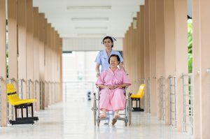 thai nurse pushing old woman in wheel chair